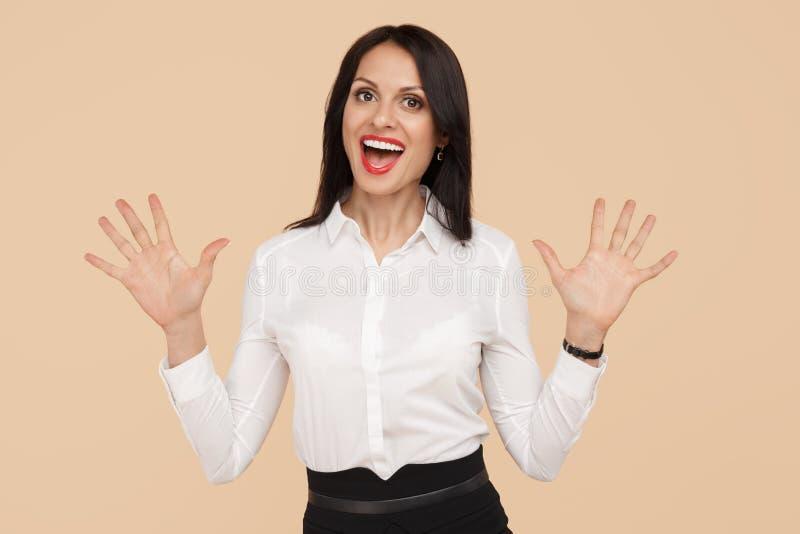Z podnieceniem młoda nowożytna biznesowej kobiety pozycja z rękami w górę nadmiernego beżowego tła Sukces i zwycięzcy pojęcie zdjęcie stock