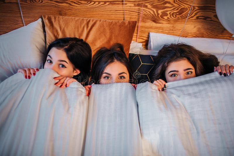 Z podnieceniem młode kobiety zakrywa część ich twarze z białą koc Patrzeją na kamerze z cudownym widokiem giro obrazy stock