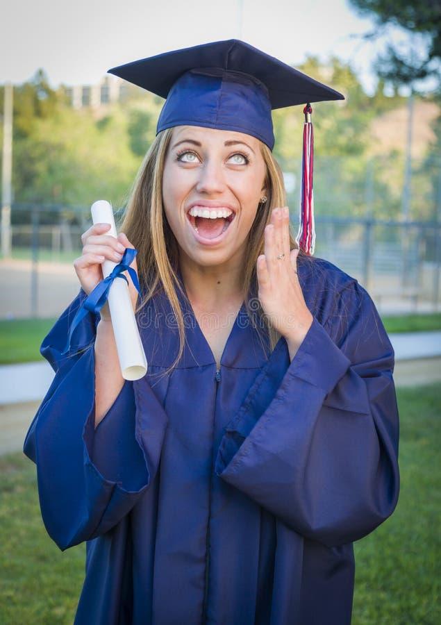 Z podnieceniem młodej kobiety mienia dyplom w nakrętce i todze fotografia royalty free