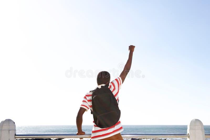 Z podnieceniem młody amerykanina afrykańskiego pochodzenia mężczyzna patrzeje morze zdjęcie royalty free