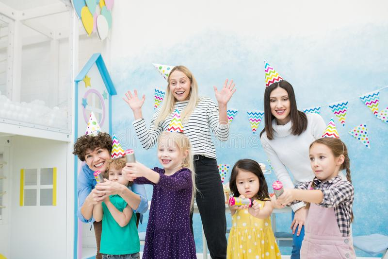 Z podnieceniem matki ma zabawę z dzieciakami przy przyjęciem urodzinowym zdjęcie royalty free