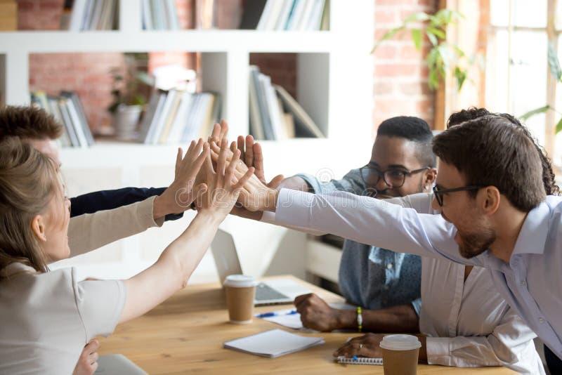 Z podnieceniem multiracial drużynowa daje wysokość pięć przy firmy spotkaniem zdjęcie royalty free