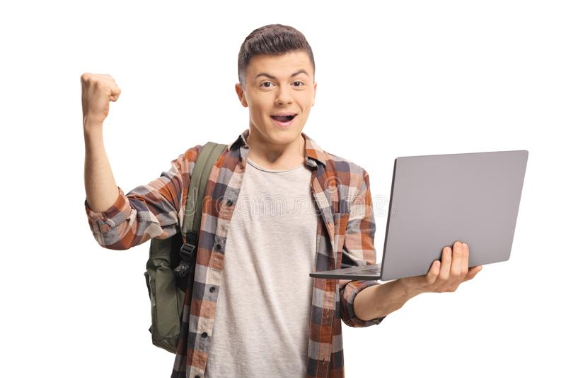 Z podnieceniem nastoletni chłopak trzyma laptop i gestykuluje z ręką obrazy stock