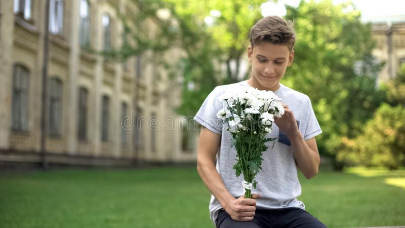 Z podnieceniem nastoletnia ch?opiec czeka? na dziewczyny z bukietem kwiaty, antycypacja obrazy royalty free