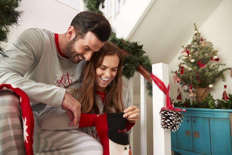Z podnieceniem para Jest ubranym piżamy Siedzi Na schodkach Patrzeje W pończochy Na poranku bożonarodzeniowy obrazy stock