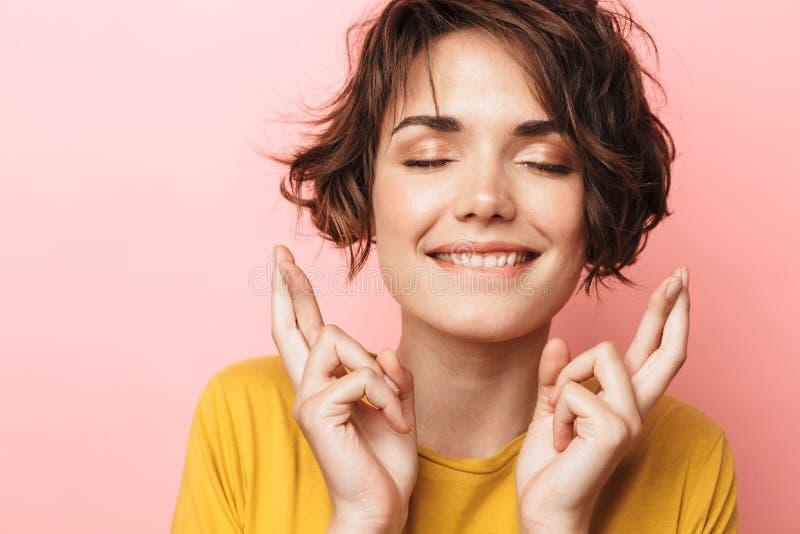 Z podnieceniem piękny kobiety pozować odizolowywam nad menchii ściany tłem robi obiecującego zadawalać gestów palce krzyżujących fotografia stock
