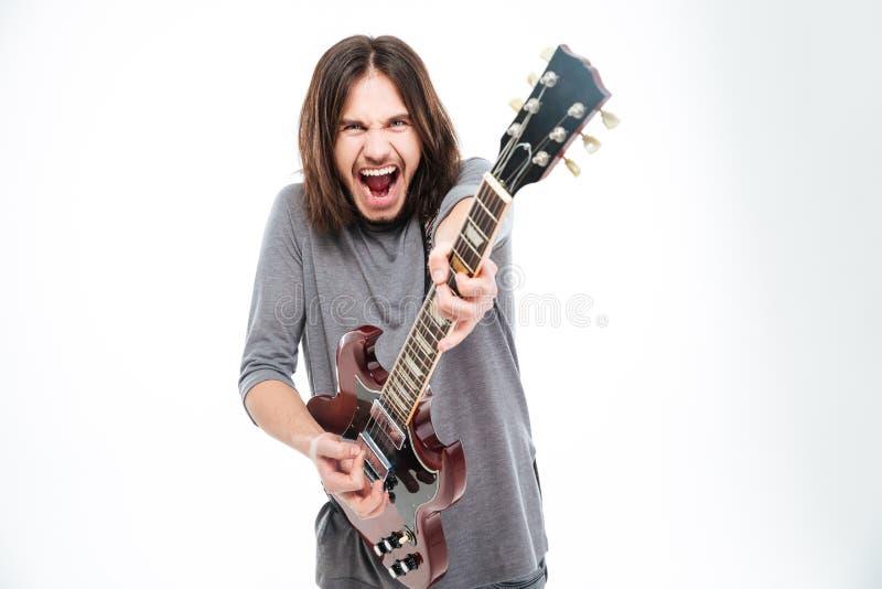Z podnieceniem popularny młody męski piosenkarz krzyczy gitarę elektryczną i bawić się obraz stock