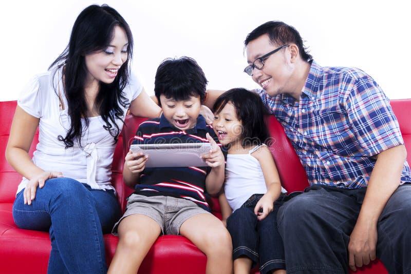 Z podnieceniem rodzinna bawić się gra na internecie - odosobnionym obraz royalty free