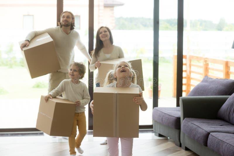 Z podnieceniem rodzinni dzieci przychodzi w nowego dom na poruszającym dniu obrazy stock