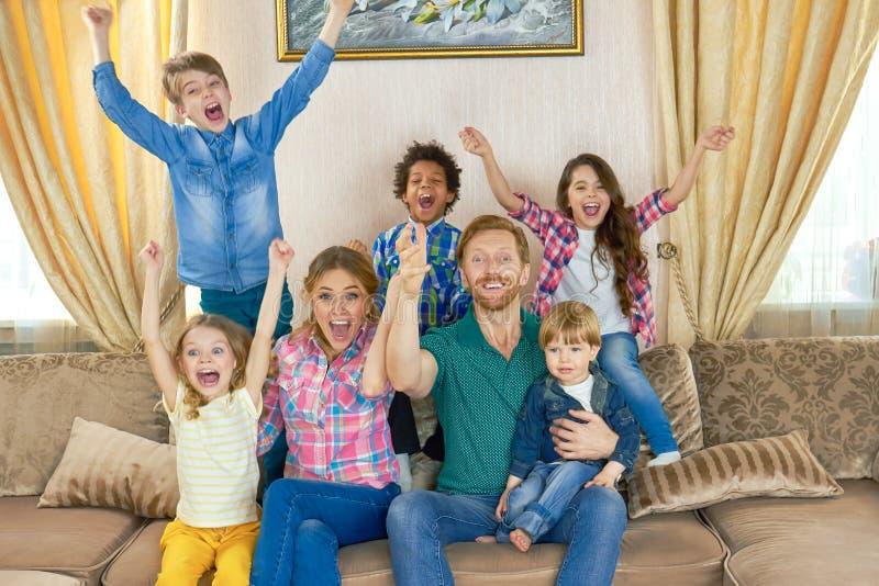 Z podnieceniem rodzinny obsiadanie na kanapie fotografia stock