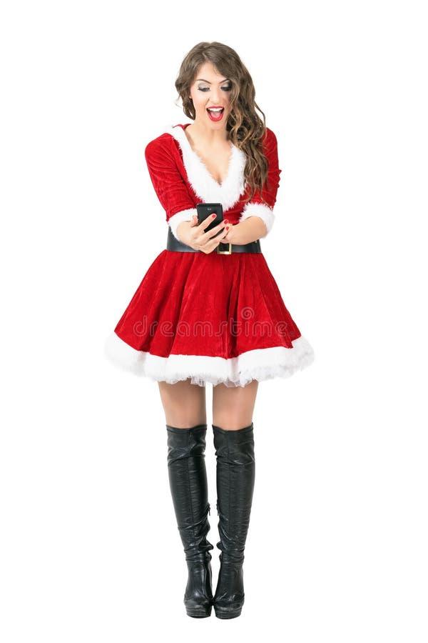 Z podnieceniem rozochoconej kobiety Święty Mikołaj pisać na maszynie wiadomość na mądrze telefonu dotyka ekranie fotografia stock