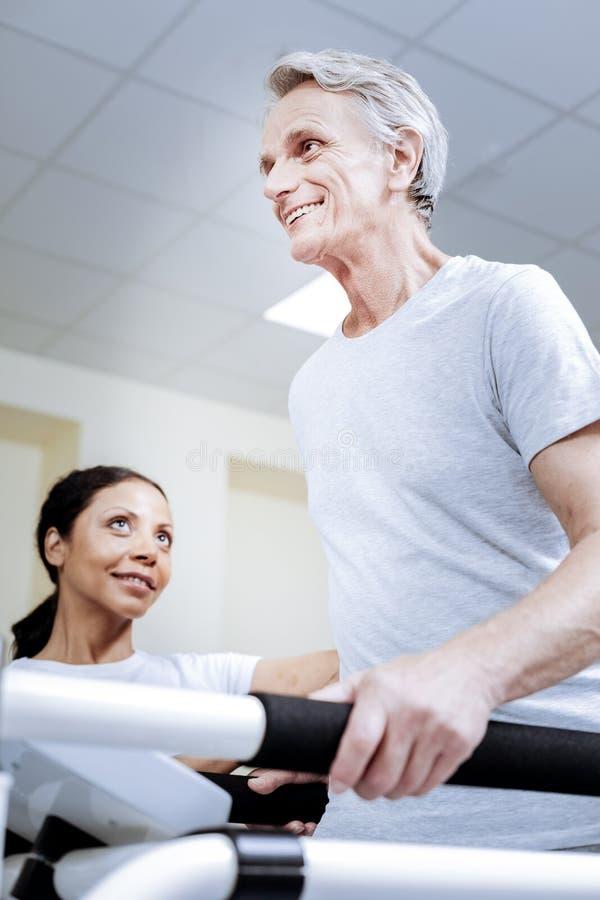 Z podnieceniem rozochocony emeryt ono uśmiecha się podczas gdy być w dobrym gym obrazy royalty free