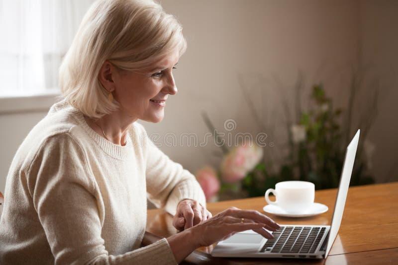 Z podnieceniem starsza dama wyszukuje sieć używać laptop w domu fotografia stock
