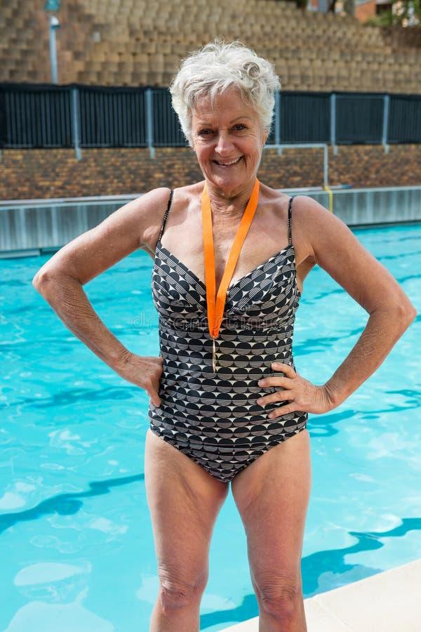 Z podnieceniem starsza kobieta z złotymi medalami wokoło jej szyi pozyci przy poolside fotografia stock