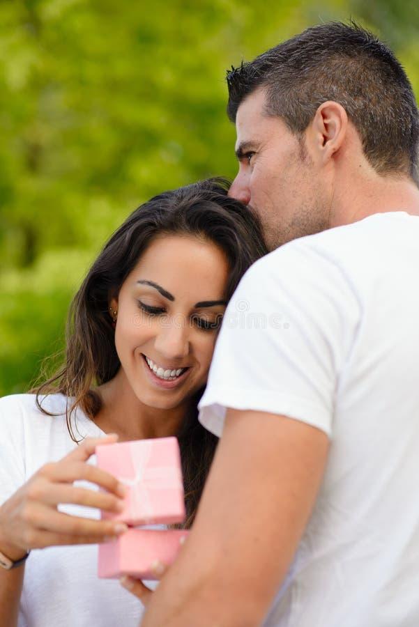 Z podnieceniem szczęśliwa kobieta otrzymywa teraźniejszość od jej chłopaka fotografia royalty free