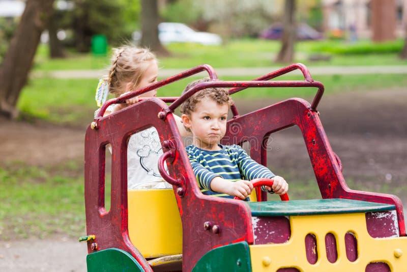 Z podnieceniem szczęśliwi dzieciaki jedzie zabawkarskiego samochód zdjęcie stock
