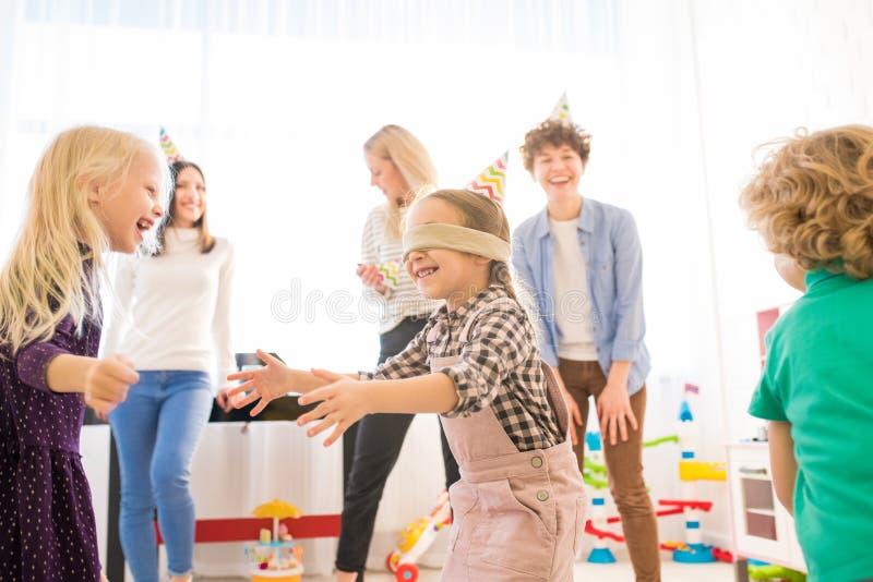 Z podnieceniem z zasłoniętymi oczami dziewczyny chwytający przyjaciele podczas gry zdjęcie royalty free