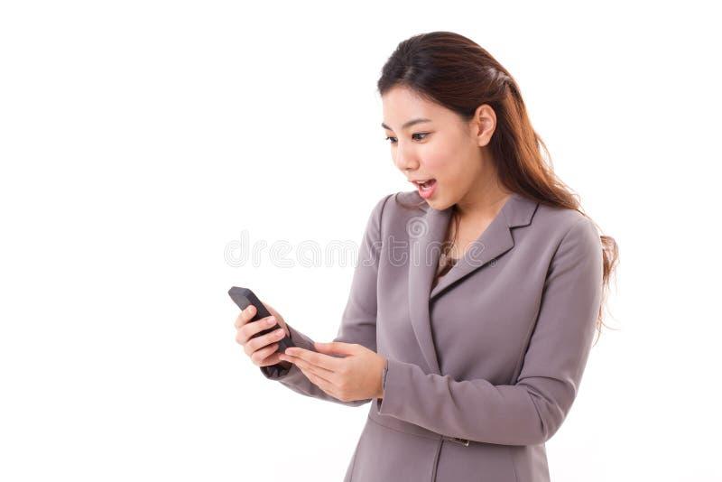 Z podnieceniem, zdziwiona biznesowa kobieta patrzeje jej telefon komórkowego, zdjęcia stock