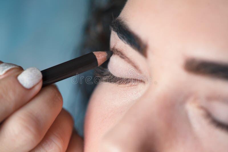 Z pomocą Kosmetycznego ołówka, maluje gęstą linię na twój rżniętym zagnieceniu obrazy royalty free