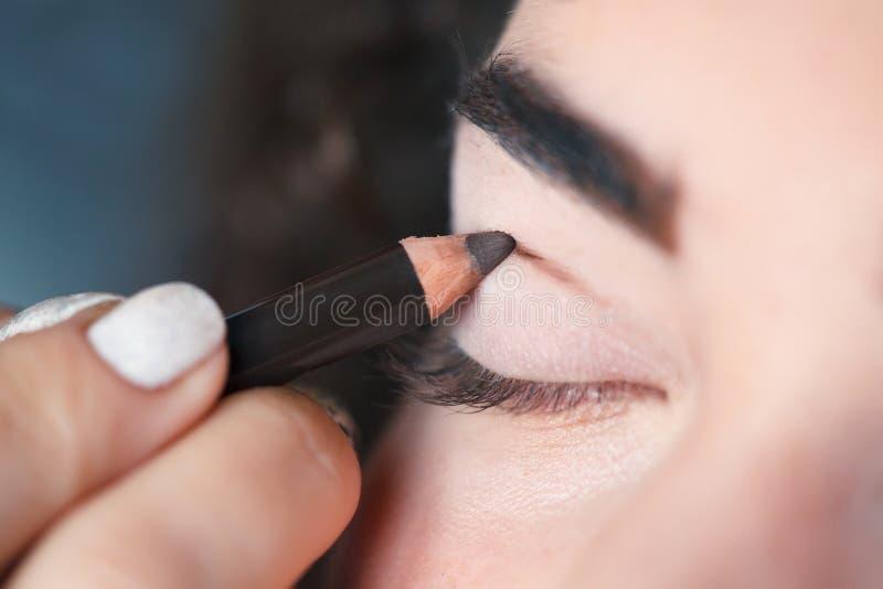 Z pomocą Kosmetycznego ołówka, maluje gęstą linię na twój rżniętym zagnieceniu zdjęcie stock