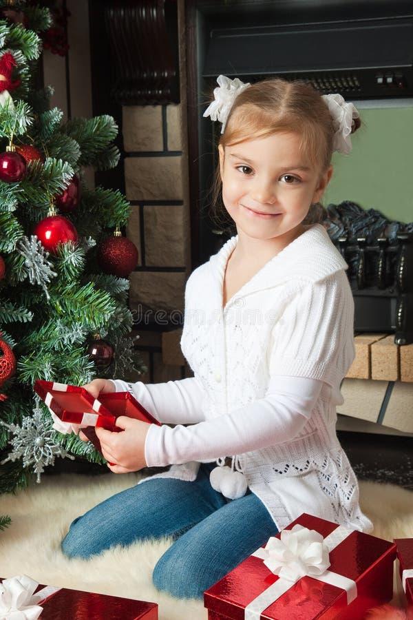 Z prezentami szczęśliwa mała dziewczynka zbliżać choinki zdjęcie stock