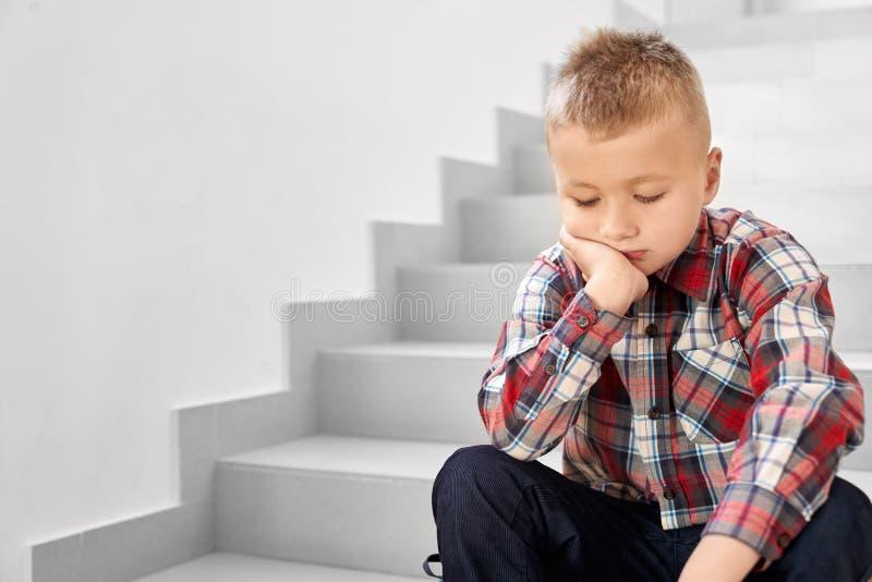 Z przykrością szkolna chłopiec na schodkach przy korytarzem szkoła i płacz obraz royalty free