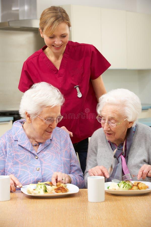 Z target1057_0_ opiekunu posiłkiem starsze kobiety w domu zdjęcie stock