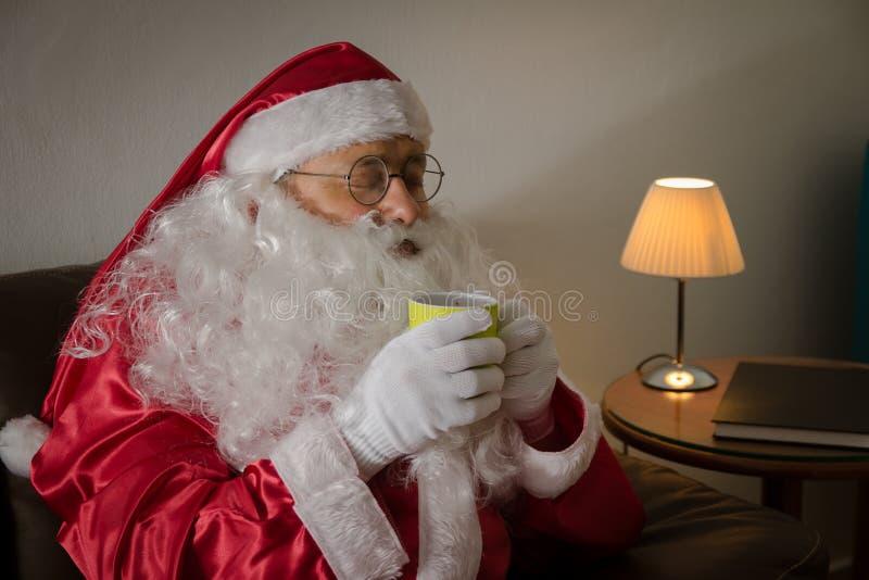 Z ukosa Święty Mikołaj relaksuje w kanapie cieszy się filiżankę w domu fotografia stock