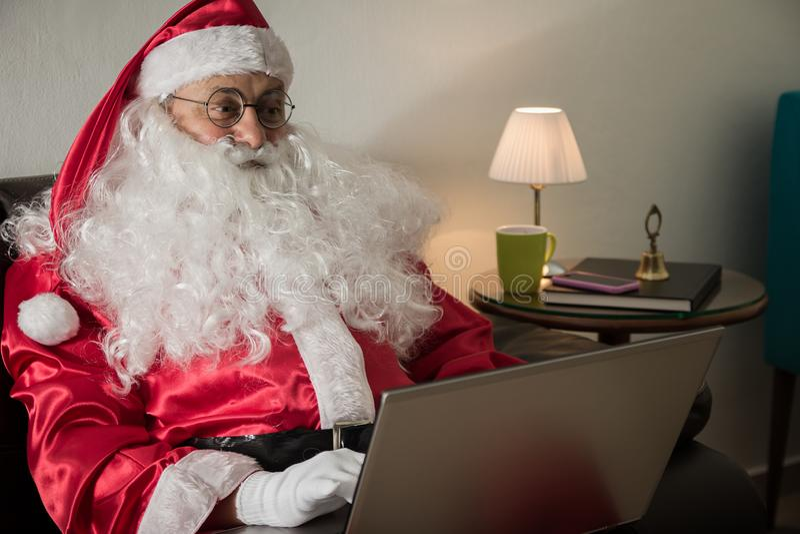 Z ukosa Święty Mikołaj relaksuje w kanapie Używa laptop fo w domu obrazy stock