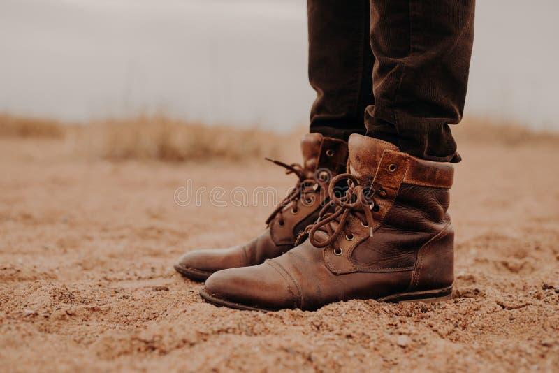 Z ukosa strzał mężczyzna w kostrzewiastych brązów butach na nieatutowej powierzchni Para buty na piasku Samiec plenerowego spacer fotografia stock