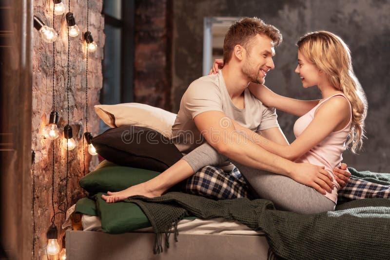 Z włosami dziewczyna ściska jej silnego przystojnego mężczyzny w łóżku obrazy stock