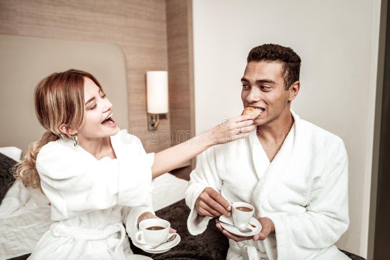 Z włosami dziewczyna daje jej mężczyźnie yummy świeżemu croissant zdjęcia royalty free