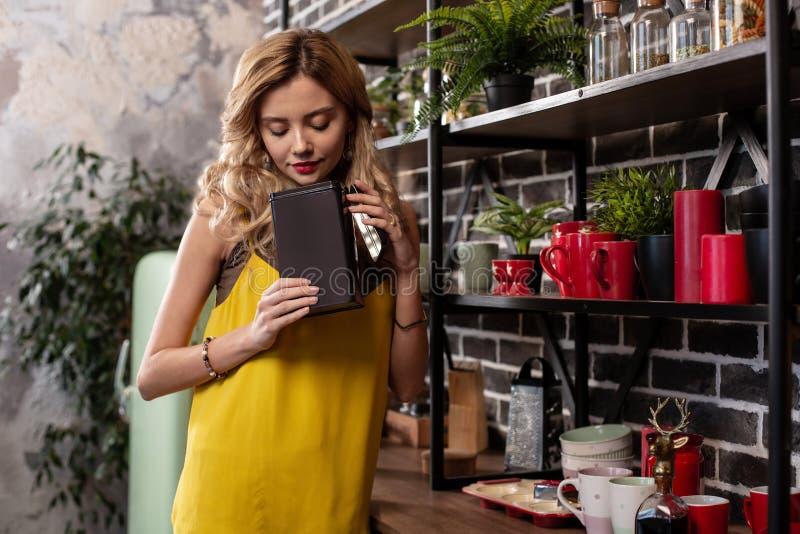 Z włosami dziewczyna jest ubranym bransoletkę bierze niektóre herbaty w kuchni zdjęcia royalty free