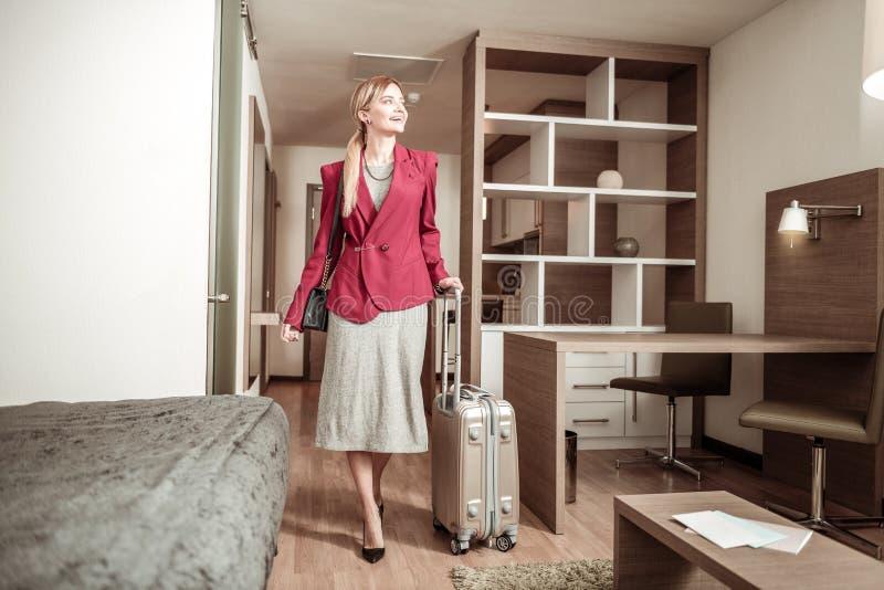 Z włosami kobieta przychodzi pokój hotelowy z jej bagażem obrazy royalty free