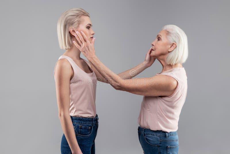 Z włosami poważne kobiety sprawdza each inny stawiają czoło obraz stock