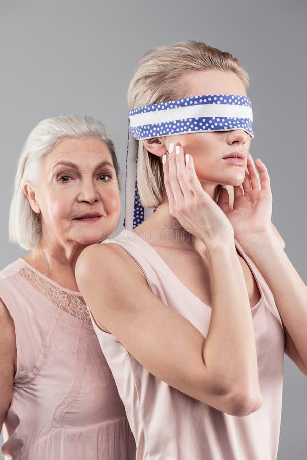 Z włosami senior matka wspiera jej z zasłoniętymi oczami interesującej córki obraz stock