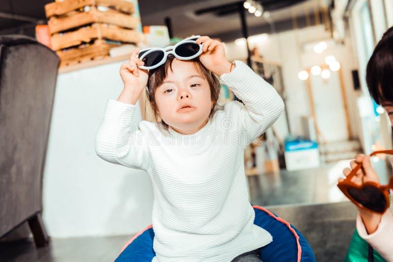 Z włosami dziewczyna zdejmuje okulary przeciwsłonecznych z umysłowymi problemami obraz stock