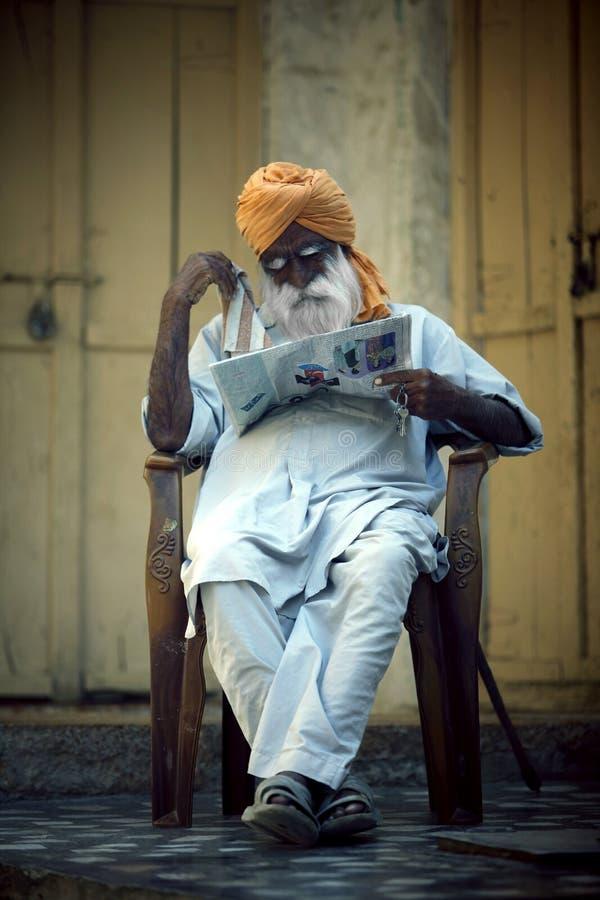 Z włosami indianin, starego człowieka obsiadanie w krześle i czytanie, gazeta zdjęcie stock