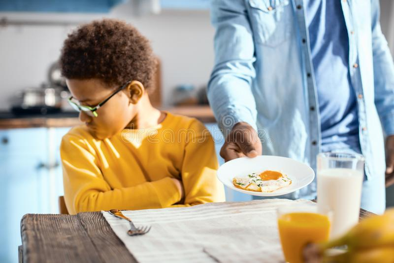 Z włosami nastoletni chłopiec odmawianie jeść smażył jajko fotografia royalty free