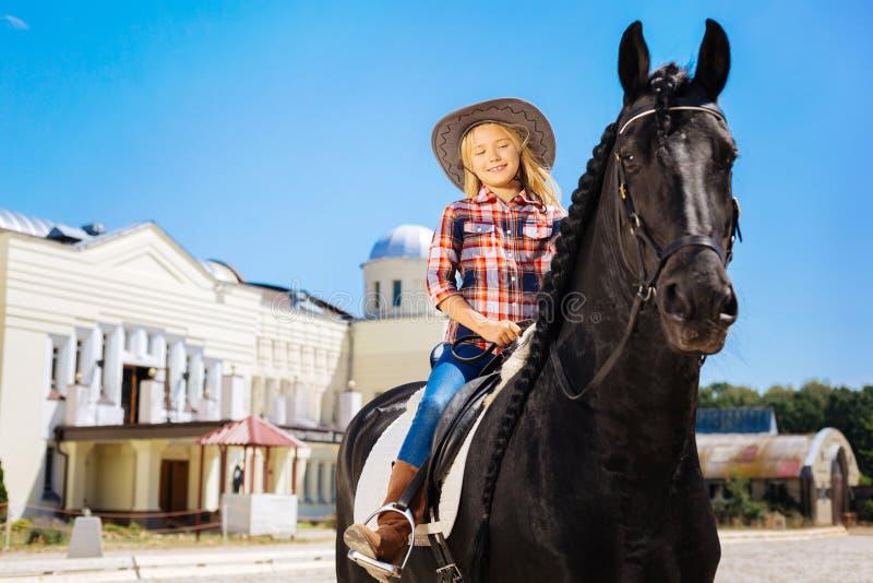 Z włosami nastoletnia dziewczyna jedzie delikatnego czarnego konia fotografia stock