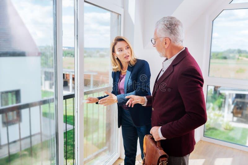 Z włosami pośrednik w handlu nieruchomościami pokazuje ładnemu balkonowi nowożytny dom jej klienta zdjęcie stock