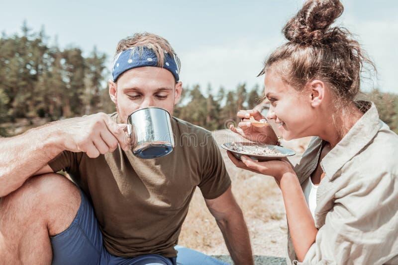 Z włosami wycieczkowicz pije gorącego herbacianego obsiadanie blisko jego dziewczyny łasowania śniadania obrazy royalty free