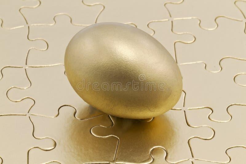 Z złocistym gniazdowym jajkiem łamigłówka kawałki fotografia royalty free