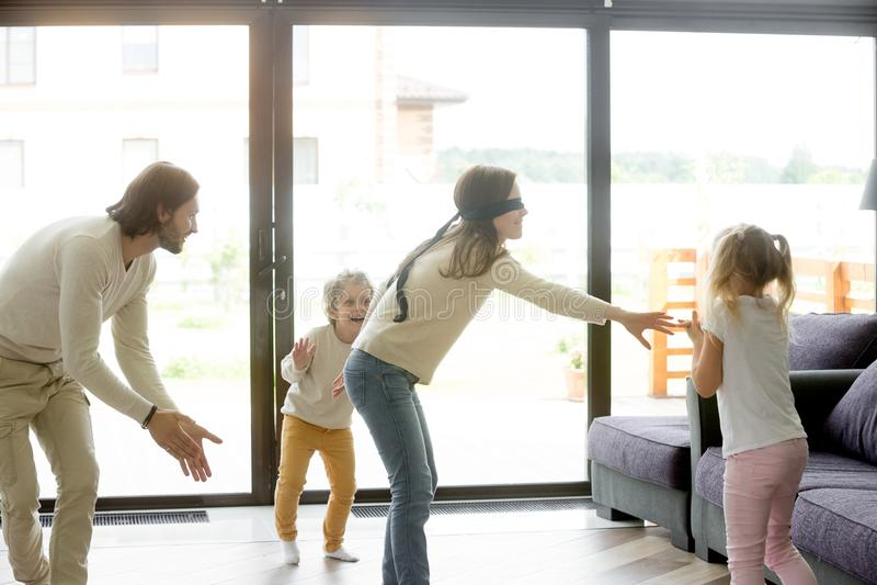 Z zasłoniętymi oczami matka bawić się kryjówkę aport gra z ojców dzieciakami - i - zdjęcie royalty free