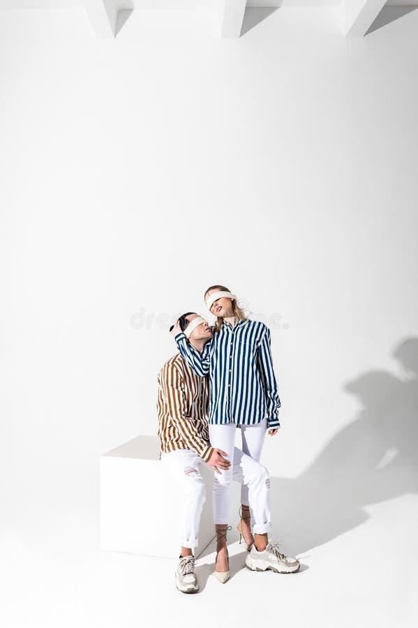 Z zasłoniętymi oczami para jest ubranym białych spodnia pozuje wpólnie modele fotografia royalty free