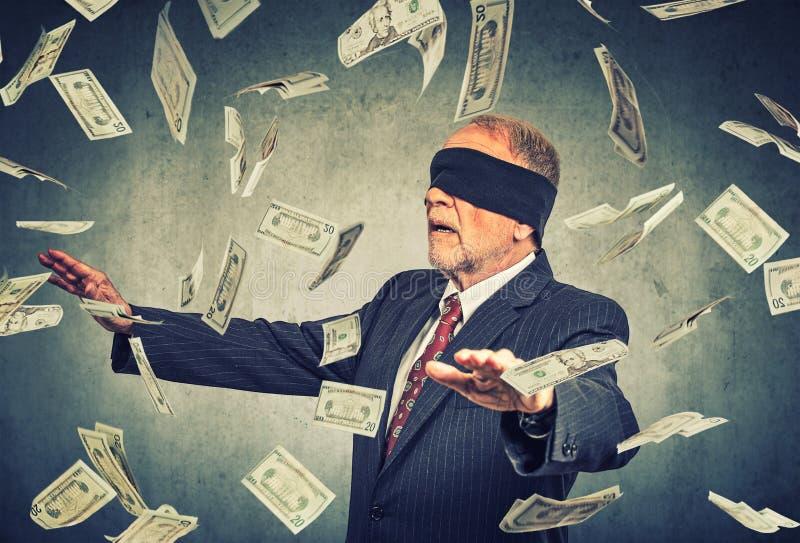 Z zasłoniętymi oczami starszy biznesmen próbuje łapać dolarowych rachunków banknoty fotografia royalty free