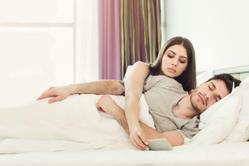 Z zazdrością żona przeszpiegi telefon mąż podczas gdy mężczyzna dosypianie fotografia stock