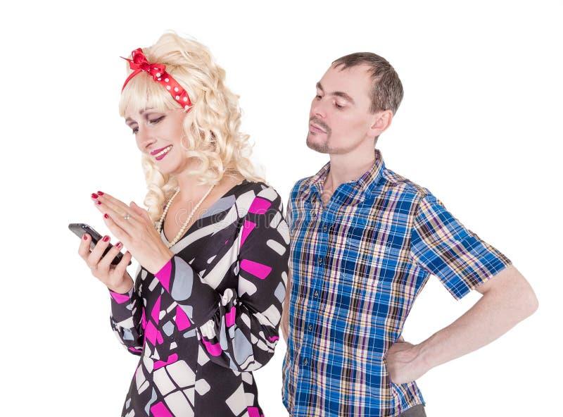 Z zazdrością mąż ogląda jego żony używa telefon komórkowego obrazy royalty free