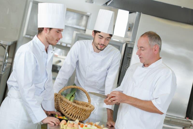 Załoga pozytywny profesjonalista gotuje działanie przy restauracyjną kuchnią zdjęcia stock
