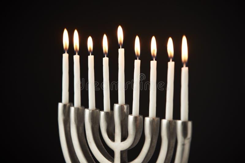 Zaświecać świeczki Na metalu Hanukkah Menorah Przeciw Czarnemu Pracownianemu tłu zdjęcia royalty free